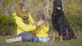 Portrait of young Caucasian woman sitting on green grass and putting mustard hat on girl. Beautiful graceful doberman sitting next to them. Mother and daughter spending time with their dog outdoors