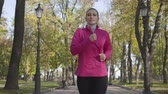 dýchat : Young Caucasian woman in sportswear and headphones running in the autumn park. Female runner training in the morning outdoors. Sports concept