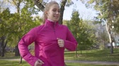 dýchat : Smiling Caucasian woman in pink sportswear and headphones running in the autumn park. Female runner training in the morning outdoors. Sports concept