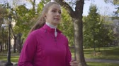 dýchat : Close-up of a smiling Caucasian girl in pink sportswear and headphones running in the autumn park. Female runner training in the morning outdoors. Sports concept