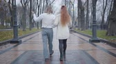 yelek : Back view of young Caucasian couple walking along the alley in autumn city park. Happy boyfriend and girlfriend having date outdoors. Unusual man and woman in retro clothes strolling