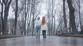 yelek : Camera following young Caucasian man with long hair and redhead woman walking along the alley in autumn city park. Happy boyfriend and girlfriend having date outdoors. Couple in retro clothes Stok Video