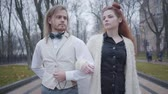 yelek : Close-up of young Caucasian couple walking arm-in-arm. Man in white shirt and vest and and plaid bow tie, and woman with double buns strolling together outdoors. Romantic date, happiness Stok Video
