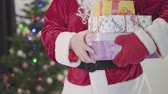 dát : Old Caucasian man in Santa Claus costume giving presents to camera in front of the New Year tree. Man holding gift boxes. Concept of happy holidays, traditions, Christmas Dostupné videozáznamy