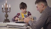 szachy : Portrait of cute smart Caucasian boy placing chess on board and talking to father sitting at the foreground and using smartphone. Son asking attention from parent in the evening. Family, relationship
