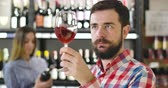vonící : Close-up of focused Caucasian man smelling red wine in glass and shaking wineglass. Confident concentrated sommelier degustating drink in luxurious alcohol market. Occupation, lifestyle, industry