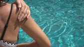 applying : video of a Woman Applying Sun Cream at the swimming pool. People 4K Stock Footage Clip.