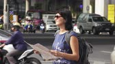 heavy : Attractive woman reading tourist map on city street with heavy traffic at background. 4K Stock Footage Clip.