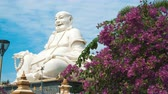 sculpture : MY THO - DECEMBER 22, 2017: Giant White Buddha sitting at Vinh Trang Temple. Clouds Run in the Sky Over the Sitting Statue. on december 22, 2017 in My Tho, Vietnam. Stock Footage