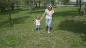 taking away : Happy young mother with little girl running on summer lawn. Family in the park. Slow motion family concept video.