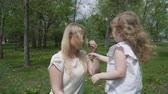 taking away : Happy little girl playing with her mother on summer lawn. Family in the park. Slow motion family concept video. Stock Footage