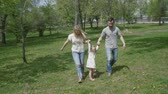 taking away : Happy young family with little girl running on summer lawn. Family in the park. Slow motion family concept video. Stock Footage