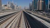 DUBAI, UAE - DECEMBER 12, 2018: Modern Dubai Metro train travels on rails along the high-rise buildings in Dubai, UAE.