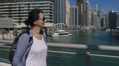 A happy woman walking street in Dubai on a background of skyscrapers at Dubai Marina. Vídeos