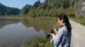 Attractive woman taking pictures of beautiful views at wetlands in Vietnam.