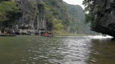 TAM COC, VIETNAM - DECEMBER 17, 2018: Panorama view of beautiful karst scenery, river and rice paddy fields. Tourists traveling in small boat along the river, Ninh Binh Province, Vietnam