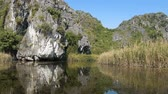 인도 차이나 : TAM COC, VIETNAM - DECEMBER 17, 2018: Panorama view of beautiful karst scenery, river and rice paddy fields. Tourists traveling in small boat along the river, Ninh Binh Province, Vietnam