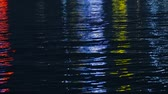 Colorful lights reflecting in the water at night, abstract background color tone.