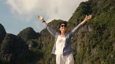 Slow motion - attractive happy woman standing and raising her hands up against high rocky mountains, admiring beautiful views, Vietnam.
