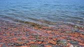 smooth water : Waves splashing on rocky beach with rounded red and gray stones on bottom.