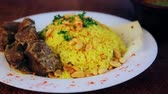 plov : Food, boiled rice with meat and peanuts. Arabic pilaf with meat sauce and peanuts.