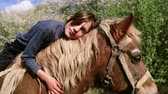 horse face : Caucasian boy teenager with a horse on nature. Rural child with a favorite pet horse. The boy takes care of his pet, a favorite horse. People, nature, animals.