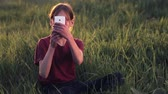 holding : Caucasian boy with the phone on the nature.Boy teenager with a smartphone at sunset.Boy with phone photographs sunset. Nature, people, and technology.