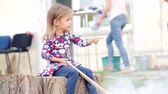 food : Little girl sitting at home near the grill. Caucasian little girl at a fire near the house.