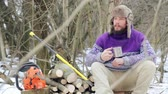 suécia : Bearded man drinking tea in the forest. Bearded woodcutter at rest in winter. Lunch have lumberjack winter.