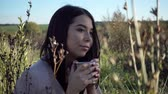 caneca : Girl drinking tea in nature enjoying the beauty. Beautiful young woman resting with a mug of coffee in nature.