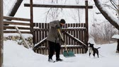 дома : A young man cleans the snow in his yard. Bearded man cleans snow near his house.