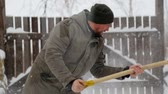 spade : A young man cleans the snow in his yard. Bearded man cleans snow near his house.