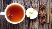 spiced : Tea composition with spices and natural herbs. A mug of tea on a textured table with cinnamon and star anise. Stock Footage