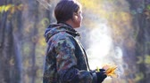 A boy walks in the autumn park. Teen scout explores the forest in autumn.