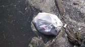 Plastic waste polluting into nature. rubbish bag floating on water Filmati Stock
