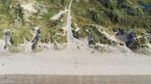 Aerial view as people walk through sand dunes on Harlech beach, North Wales