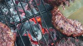 karakalem : Slow motion of organic burgers being turned over on a BBQ Stok Video
