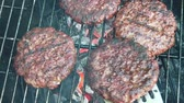 Slow motion of organic burgers being turned over on a BBQ Filmati Stock