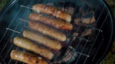 chargrilled : Bratwurst sausages cooking on a wood barbecue Stock Footage
