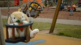 swinging soft toy bunny on the children playground. Blurred mum with toddler kids
