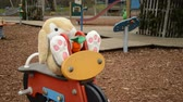soft toy rabbit sitting on the play equipment in the empty children playground