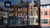 town traffic in the mirror of building. Transport and  passengers movement. Information display at a bus stop. Ipswich, Suffolk, East England.  2016