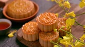 desvanecer : Beautiful Moon cakes on a wooden tray with tea and flower on black slate background. Chinese traditional Mid-Autumn Festival concept. Truck right.