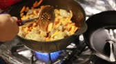 pilau : Starting to cook pilaf, shef stirs meat with carrots in a cast-iron kettle