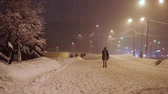 wintertime : pedestrians hurry along sidewalk under abnormal snowfall in the evening Stock Footage