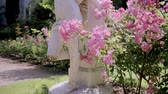 melek : sculpture of fallen angel through Flowering bushes in the rose garden