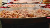 espanhol : Preparation of a giant paella. Meat is cooked in large frying pans and produces steam.