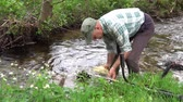 A man washes the trimmer in the creek. Dostupné videozáznamy