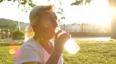 hidrasyon : Adult woman sits in a park and drinks water from a plastic bottle in the sun. Outdoor recreation Stok Video