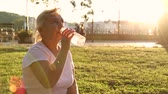 hidratáció : Adult woman sits in a park and drinks water from a plastic bottle in the sun. Outdoor recreation Stock mozgókép